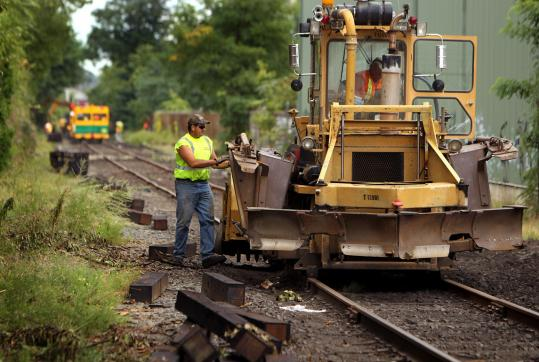 Workers pull up old railroad ties to replace them along the Grand Junction railroad. The work is necessary to bring the tracks up to the standard for passenger rail service.