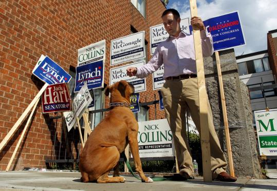John Cotter of South Boston and his dog, Braddock, backed their candidate on L Street. Turnout was light across the state.