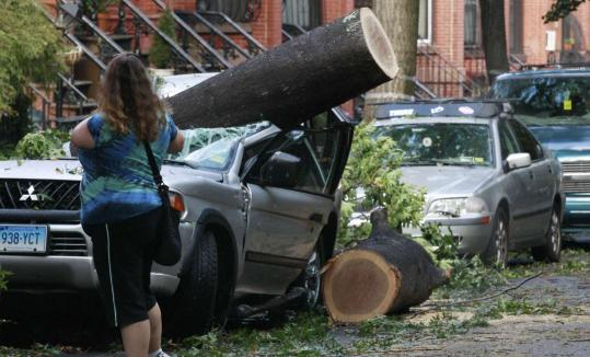 A woman took pictures of a tree-damaged car in the Park Slope section of Brooklyn, N.Y., yesterday. A severe storm hit the metropolitan area Thursday evening.