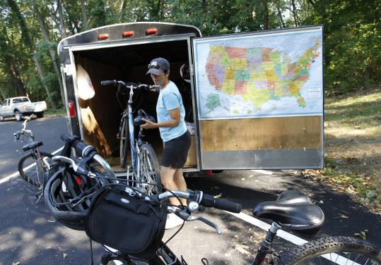 Sue Merlino takes bikes off a trailer at the parking lot of the North Bridge in Concord, where her cycling tour of local antislavery sites begins.