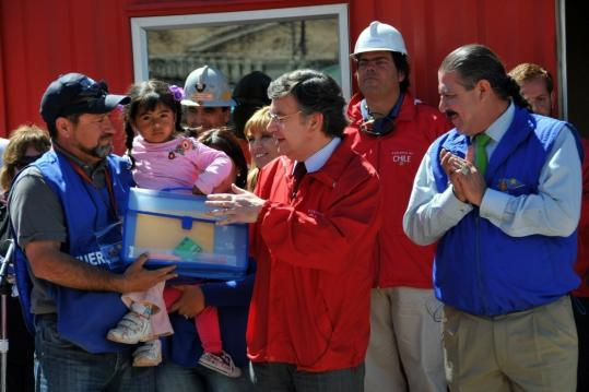 Joaquin Lavin (center), Chile's education minister, gave a bag of school supplies to a child relative of one of the trapped coal miners during a visit to the San Jose mine yesterday.