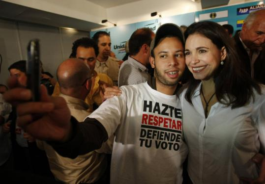 Independent opposition legislative candidate Maria Corina Machado celebrated with a supporter in Caracas yesterday.