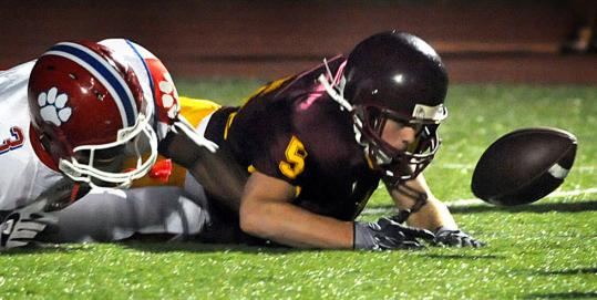 Weymouth's Austin Colarusso (No. 5) fights Milton's Shamari Welles for a loose ball Friday.