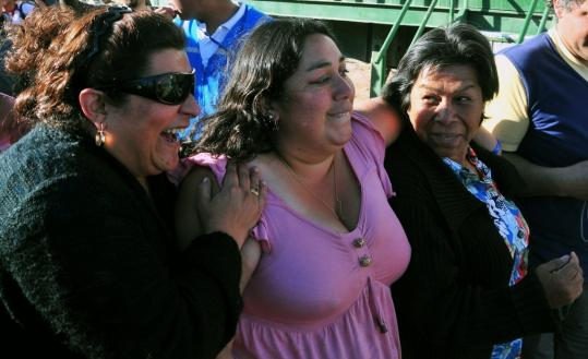 Jessica Cortez (center) and Nelly Burgueno (right) — the wife and mother of Victor Zamora, one of the 33 trapped miners — reacted after hearing of the unexpected progress in rescue efforts.