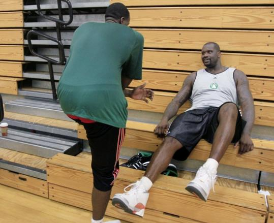 Celtics center Kendrick Perkins (left), out after surgery on his right knee, is helping the coaching staff in training camp; he chats with newcomer Shaquille O'Neal after practice.