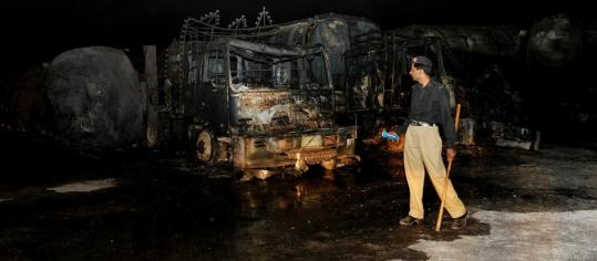 Heavily armed gunmen in the Shikarpur district of Pakistan set ablaze more than two dozen trucks and tankers carrying fuel and supplies for NATO forces in Afghanistan yesterday.
