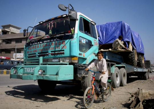A child pedals past a truck carrying supplies for NATO forces, parked yesterday along the roadside in Pakistan. About 150 truck drivers awaited reopening of the border crossing at Torkham so delivery of supplies to troops in Afghanistan could proceed.