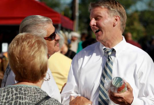 Timothy P. Cahill, holding a jar of marinara, shared a laugh yesterday with Toffee and Linda Derbes at a farmers market in Braintree.