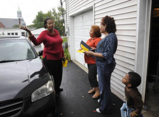 Maria Agosto (center) visited her neighbors on Dumais Street in Fitchburg last week, bringing them recycling information.