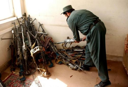 An Afghan policeman inspected weapons Saturday that were collected from a private security company in Herat.