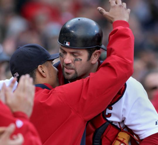 Red Sox catcher Jason Varitek gets a hug from Victor Martinez after he was replaced in the ninth inning yesterday.