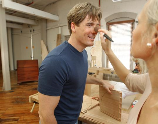 Tommy MacDonald gets a touch-up from makeup artist Sonja Gjokaj during the shooting of MacDonald's show, ''Rough Cut,'' in his Canton studio.
