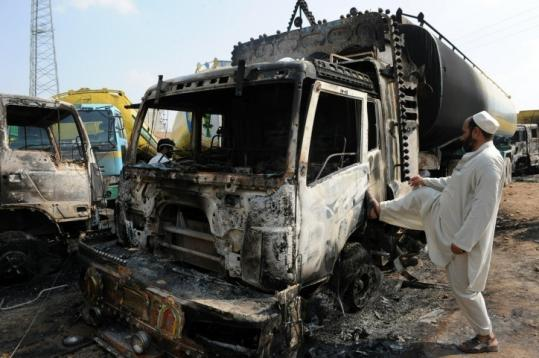 Truck owners examined a heavily damaged NATO supply oil tanker hit in an attack on the outskirts of Islamabad, Pakistan.