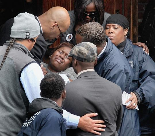 A mourner was overcome with grief after a funeral yesterday for shooting victim Simba Martin, 21. The 90-minute service carried about 400 people through somberness, laughter, and foot-tapping worship.