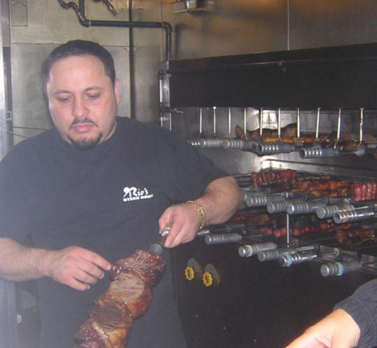 Chef Robson Oliveira (above) skewers cubes of meat at Rio's Brazilian Steakhouse in Quincy. Waiters move around the room with platters of skewered beef, pork, chicken that are offered to buffet diners. The buffet also includes a variety of hot and cold side dishes.