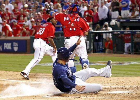 Carlos Pena, who had tied the game three batters earlier, slides home with the Rays' go-ahead run in the eighth inning.