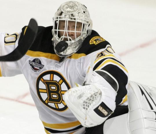 Tim Thomas looked sharp — including his new black and white one-piece mask — during his season debut Sunday in Prague.