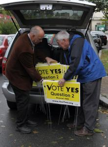 John Belskis (right), chairman of the Coalition to Repeal 40B, handed out signs to Joe Ureneck in Dorchester on Friday.