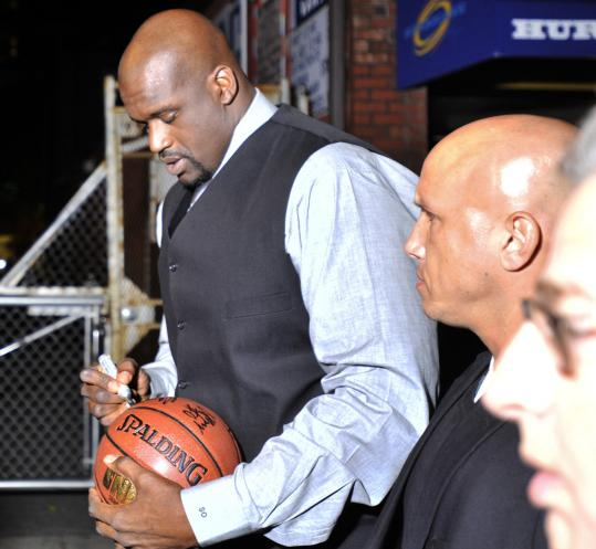Shaquille O'Neal signs a basketball for a fan on his way into the Greatest Bar on Monday night.