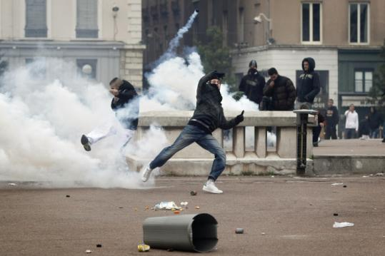 Young protesters threw tear gas grenades back toward police in Lyon. They oppose plans to raise France's retirement age.