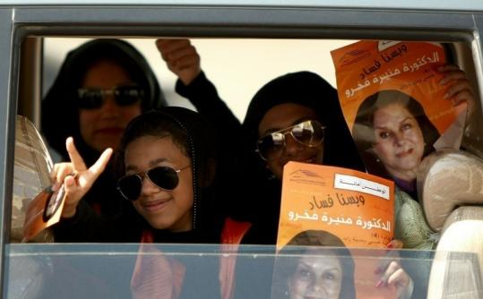 Supporters of parliamentary candidate Mounira Fakhro held her posters outside a polling station yesterday in Isa city.