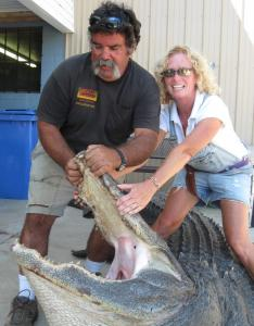 Maryellen Mara-Christian, with husband Mark Christian, proudly displays her recent catch: a 13-foot-6-inch alligator.