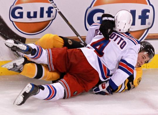 Rangers defenseman Michael Del Zotto (No. 4) checks Bruins center Tyler Seguin into the boards during the third period.