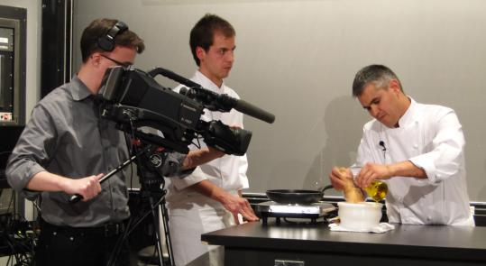 "Catalan chef Nandu Jubany (right) prepares aioli with a mortar and pestle at the ""Science and Cooking'' lecture series at Harvard. Matias Coll (left) is an assistant."