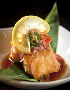 Crispy tempura sea bass is paired with red onion, cherry tomatoes, and shaved jalapeno.