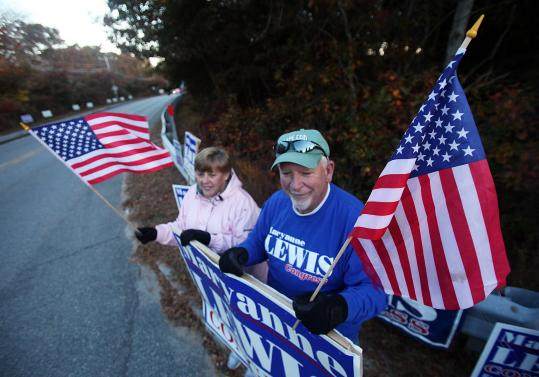 Before a candidates' forum, Betty and Bill Brackett of East Falmouth held signs for Maryanne Lewis at the entrance to Cape Cod Community College.