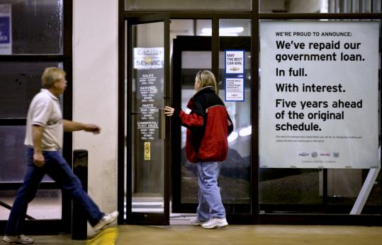 At the Stevinson Chevrolet West dealership in Lakewood, Colo., customers walked past a sign announcing General Motors Co. has paid back its US government loan in full, ahead of the original schedule.