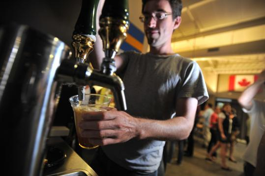 Lee Butterman, a software engineer, grabs a beer from TripAdvisor's office kegerator.