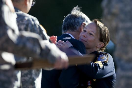 Police officer Kim Munley and Army Secretary John McHugh embraced as he presented her with an award of valor at a memorial service on yesterday's anniversary of the Fort Hood killings.