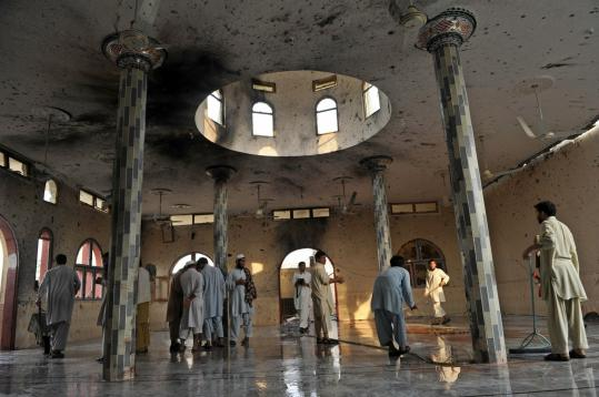 Pakistani villagers cleaned the interior of a mosque in Darra Adam Khel following a suicide bombing that killed at least 67 people during the main weekly prayers. The mosque is in an area favored by anti-Taliban militias.