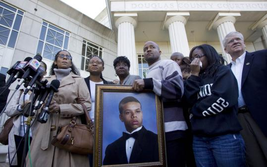 Monique Revaida (far left) is the mother of Bobby Tillman, 18, whose portrait was shown in front of the Douglas County Courthouse. Police say a group of partygoers decided to attack the next man who walked by, and Tillman was fatally injured.