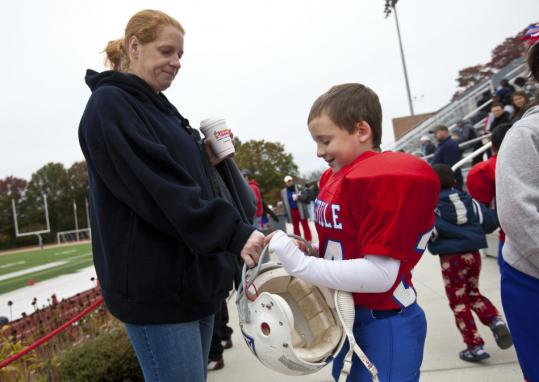 Bonnie Raposo greeted her 7-year-old son Nicholas after he played for Somerville in a Pop Warner game against Newton at Dilboy Field.