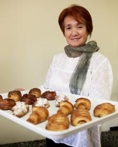 Hiroko Sakan of Japonaise Bakery & Cafe holding a tray of almond, apple, and plain croissants and maple pecan rolls.