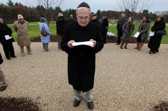 Dr. Ben Pilch of Acton reads the program before last Sunday's dedication and consecration service for the new Beit Olam East cemetery in Wayland.