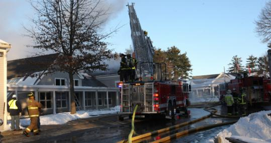 A scene from last December shows firefighters battling in vain to save the Gifford School&#8217;s Fenn Center; the Weston school is on its way to replacing the building in time for graduation in May.