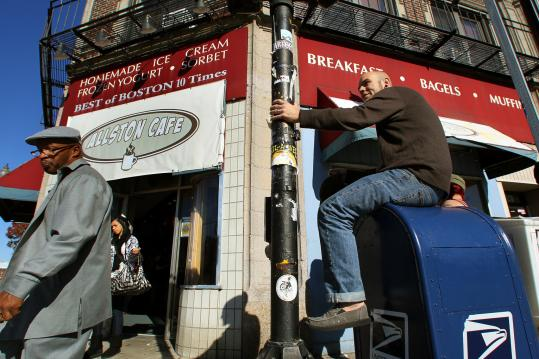 Mike McGonnell, a five-year patron of the Allston Cafe, sat atop his usual mailbox perch outside the establishment yesterday. The popular hangout on Brighton Avenue in Allston will close today because the operators cannot afford the rent increase.