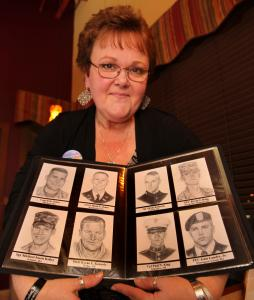 Gina Johnson, with portraits she has drawn. For the past three years, she's focused on New Englanders who have fallen in war.