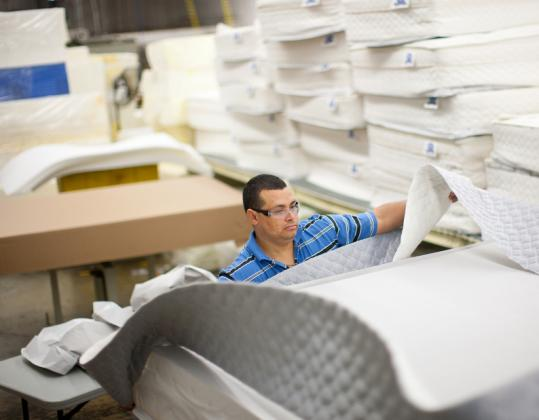 Santos Artica worked on assembling a customized king-size mattress at a Create-a-Mattress plant in Chelsea.