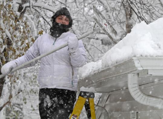 Micaela Pommerening cleaned the roof of her garage on Saturday in St. Louis Park, Minn. Almost a foot of snow fell in the region.