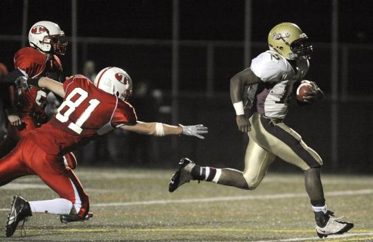 Concord-Carlisle Regional's George Craan outruns Tyngsborough High defenders en route to scoring his team's third touchdown in Friday's 43-21 win.