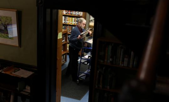 Director Daniel Johnson reshelves books in the Hull Public Library, which was unable to collect a state grant for lack of matching funds.