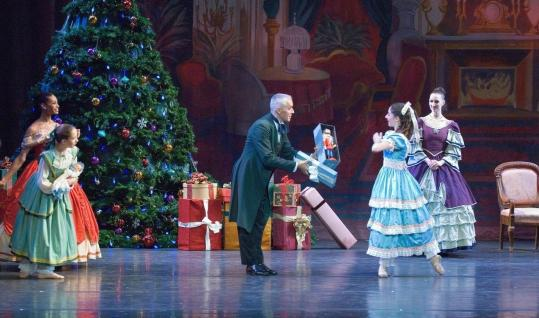 Dr. Drosselmeyer (José Mateo) gives the Nutcracker to Clara in the José Mateo Ballet Theatre production.