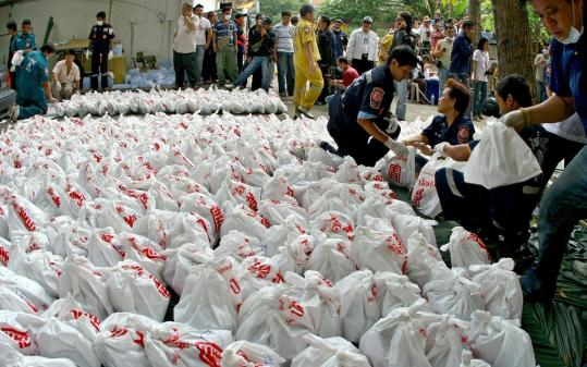 Members of a rescue foundation carried bags of remains yesterday. A strong stench had drawn police to the temple.