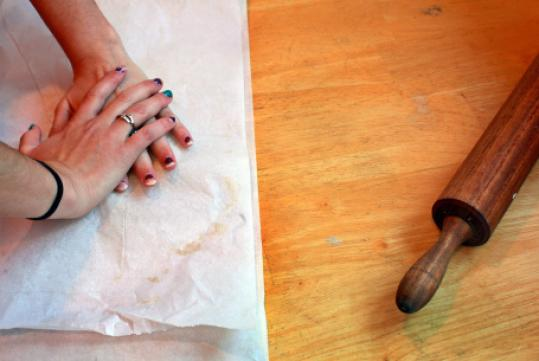 Jenny Olins presses her dough between sheets of parchment paper before rolling it