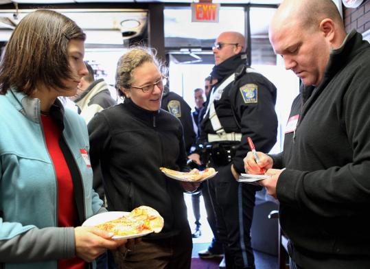 Joseph Porcelli of Neighbors for Neighbors made name tags for Theresa Vela and Melissa Behrle at a community lunch at Same Old Place in Jamaica Plain yesterday. The gathering was to show support for the pizzeria where three men were killed.