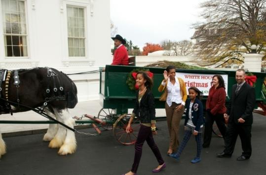 Malia, Michelle, and Sasha Obama and Brandi and Chris Botek walked alongside a carriage carrying the White House Christmas Tree. The 18 1/2-foot Douglas fir is from Chris Botek's farm in Lehighton, Pa.
